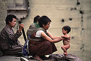 Bath time for Zekom on the ledge of her mother Nalim's home. Shingkhey Village, Bhutan. Nalim carries her grandson Tandin Geltshin in a sling on her back. The two children are the same age. From Peter Menzel's Material World Project.