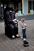 Busking invisible man accepts money from a little girl at Covent Garden, Central London. In this area there mime style street performers gather.