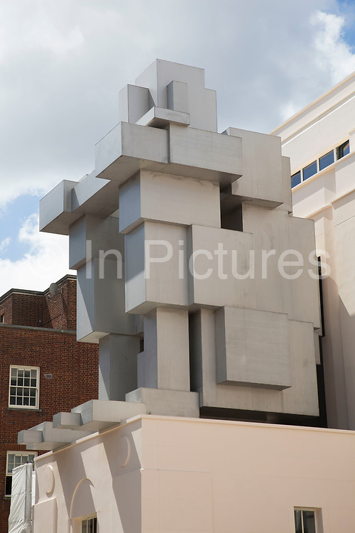 The facade of the new Beaumont Hotel in London, UK, has been topped by a large scale crouching figure by British artist Antony Gormley. 'Room' is a geometric liveable space formed with stacks of metallic cubes arranged to resemble a giant sitting man. This has been a controversial construction in amongst old architecture in Mayfair.