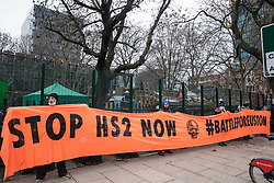 London, UK. 31 January, 2021. Anti-HS2 activists from umbrella campaign group HS2 Rebellion stand alongside Euston Square Gardens with a 'Stop HS2 Now - Battle for Euston' banner. Climbers from the National Eviction Team (NET) are currently dismantling a camp built by activists, five of whom still occupying tunnels beneath the camp, in order to seek to protect trees from felling by HS2 Ltd in connection with the controversial HS2 high-speed rail project.