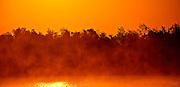Sea mist rising in front of distant mangroves is lit by the early morning sun over Plate Creek Bay, Everglades, Florida