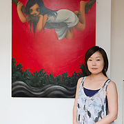 """VENICE, ITALY - JUNE 02:  Artist Rieko Sakurai  poses  in front of """"I hate this fate"""" a painting  part of the Exhibition Future Pass on June 2, 2011 in Venice, Italy. The Venice Art Biennale will run from June 4 to November 27, 2011."""