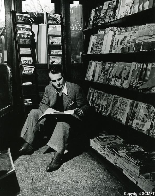 1945 Helmut Dantine reading magazines at Schwab's Drugstore