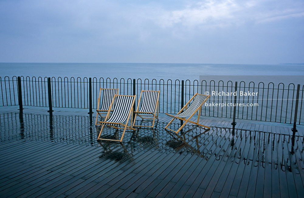 Four water-logged deckchairs have been abandoned on a wet Brighton's East Pier in East Sussex. It is Spring but the rain has driven away holidaymakers from this desolate and depressing spot from England's South coast seaside resort. We see a gloomy, grey sky and empty horizon with neither people, nor water activity but the stripes of the railings are echoed in the reflective wooden planks on this Victorian-era pier and of the fabric on the deckchairs. We wonder who might have sat on these chairs and where they might be now?  This landscape might be the antithesis of a holiday poster that repels rather than attracts tourists to this location.