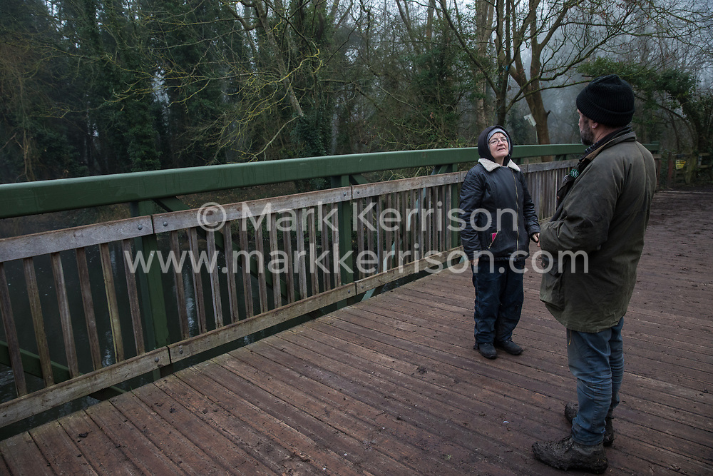 Denham, UK. 5 February, 2020. Sarah Green and Mark Keir of Save the Colne Valley monitor works for the HS2 high-speed rail link close to the river Colne at Denham Ford in Denham Country Park. Imminent works for the immediate vicinity are believed to include the felling of 200 trees and the construction of a Bailey bridge, compounds and fencing. One side of the river bank lies within a wetland nature reserve forming part of a Site of Metropolitan Importance for Nature Conservation (SMI).