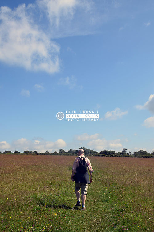 Man walking through meadow, Carew, Pembrokeshire, South Wales 2021. MR