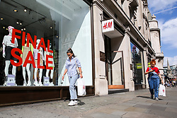 © Licensed to London News Pictures. 09/08/2019. London, UK. Shoppers holding a H&M shopping bag walks past a H&M Store on Oxford Street in London as UK retailers experience worst July since sales records began. Photo credit: Dinendra Haria/LNP