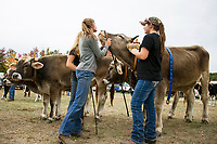 Kameron Gallant of Wheelock, VT and Shelbi Whitman of West Paris, ME wait for the working steers show on Saturday afternoon at the Sandwich Fair.  (Karen Bobotas/for the Laconia Daily Sun)