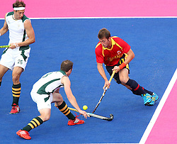 Xavi Lleonart of Spain tries to break the defence of Andrew Cronje of South Africa and Justin Reid-Ross  of South Africa during Pool MA Hockey  match between South Africa and Spain held at the Riverbank Arena in Olympic Park in London as part of the London 2012 Olympics on the 3rd August 2012..Photo by Ron Gaunt/SPORTZPICS