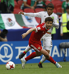 June 24, 2017 - Kazan, Russia - Yury Zhirkov (L) of Russia national team and Jonathan Dos Santos of Mexico national team vie for the ball during the Group A - FIFA Confederations Cup Russia 2017 match between Russia and Mexico at Kazan Arena on June 24, 2017 in Kazan, Russia. (Credit Image: © Mike Kireev/NurPhoto via ZUMA Press)