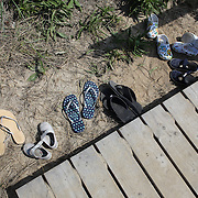 A collection of flip flops and sandals left at the top of the steps at Cisco Beach, Nantucket, Nantucket Island, Massachusetts, USA. Photo Tim Clayton