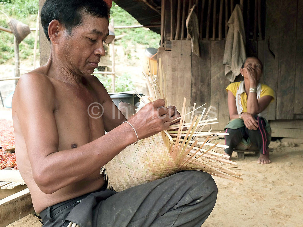 A Khmu man weaving a bamboo sticky rice basket whilst his wife smokes a homemade cigarette outside their home in Ban Phatao, Phongsaly province, Lao PDR. Renowned for their superior basket weaving skills, the Khmu belong to the Mon-Khmer language group considered to be the original inhabitants of Laos and are the largest ethnic minority with many sub-groups resident in all provinces of Northern Laos. Ban Phatao will soon be temporarily relocated away from the Nam Ou river due to the construction of the Nam Ou Cascade Hydropower Project Dam 5.