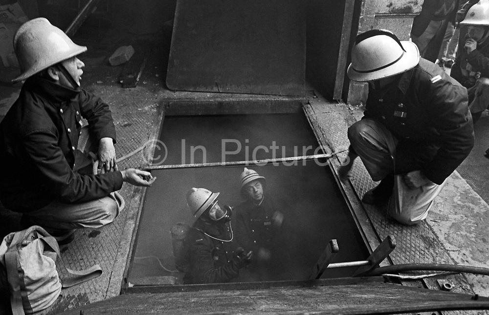 Smoke has been discovered in the basement of a shop in Market Street, Newport town centre, south Wales. We look down into a dark hole where two fire fighters – one of which is a senior officer, with two stripes on his helmet - have gone down a ladder to find the source of the smoke while wearing breathing apparatus (BA) as a precaution.  While looking up they discuss the possibilities of a seat of fire elsewhere so they talk to their colleagues who crouch over the open floor of the business who dialled 999 for the fire brigade to attend this incident. It is 1984 and the firemens' equipment looks dated, during an era when uniform material was not of a high fire-retardant specification and nor were their helmets which went through important design changes.