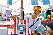Hmong man age 21 wears decorative sunglasses sells CD music disks.  Hmong Sports Festival McMurray Field St Paul Minnesota USA