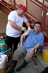 08 Sept 2005. New Orleans, Louisiana. Hurricane Katrina aftermath.<br /> The Daily Mirror's Aidan McGurran gets his hepatitis A and B and tetanus shots from paramedic  Ken Janik from Cleveland, Ohio at a makeshift clinic at the 2nd precinct in uptown New Orleans.<br /> Photo; ©Charlie Varley/varleypix.com