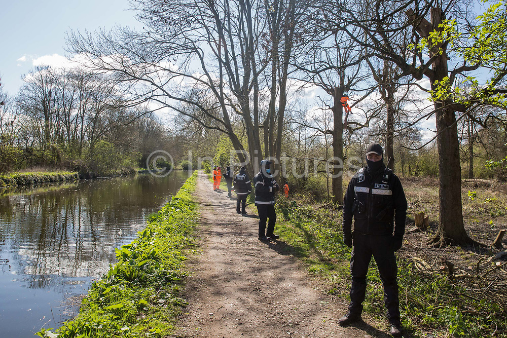 National Eviction Team NET enforcement agents stand on the towpath alongside the Grand Union Canal during tree felling in Denham Country Park for electricity pylon relocation works connected to the HS2 high-speed rail link on 6th April 2021 in Denham, United Kingdom. Large swathes of the Colne Valley have been cleared of trees and vegetation for HS2 works which will include the construction of a Colne Valley Viaduct across lakes and waterways.