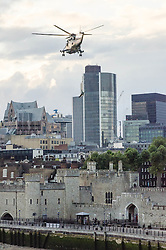 © Licensed to London News Pictures. 20/07/2012. London, UK.  London 2012 Olympics - the Olympic Torch arrives in London, flown by Royal Navy Sea King helicopter to the Tower of London and abseiled down by a Royal Marine Commando. Photo credit : Richard Isaac/LNP