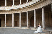 The Alhambra Palace and fortress complex located in Granada, Andalucia, Spain. Wedding couple have their pictures taken inside the pillared circular interior of Palacia de Carlos V (The Palace of Charles V). Museum of the Alhambra, Museum of Fine Arts.