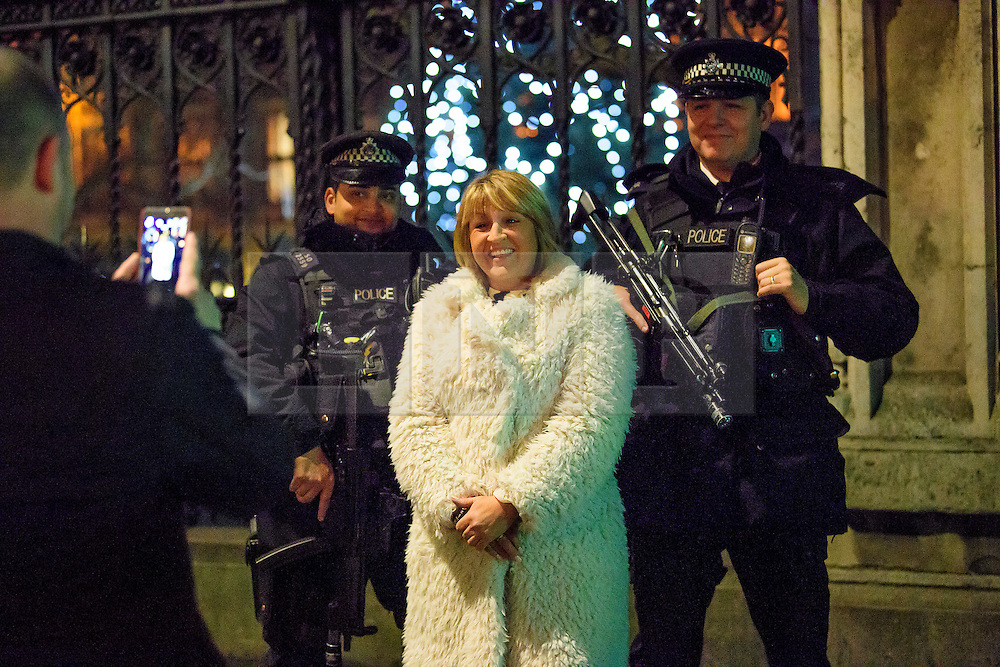 © Licensed to London News Pictures. 31/12/2016. London, UK. Two armed police officers pose for a photograph with a member of the public during tonight's New Year celebrations. Security surrounding this year's event has been heightened following a terrorist attack at a Christmas market in Berlin earlier this month. Photo credit: Ben Cawthra/LNP