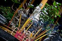 Half burnt and burning incense sit in the metal burner at Quan Su Temple in Hanoi.