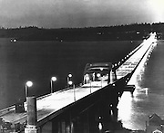 Glowing like magic, the Lake Washington Floating Bridge is shown here as it beckoned to Seattle residents after the brilliant sodium vapor lamps had been lighted for the first time. The lights are so strong that the entire expanse of the bridge and the quiet waters of the lake appeared to be bathed in sunshine. (Hack Miller / The Seattle Times, 1940)