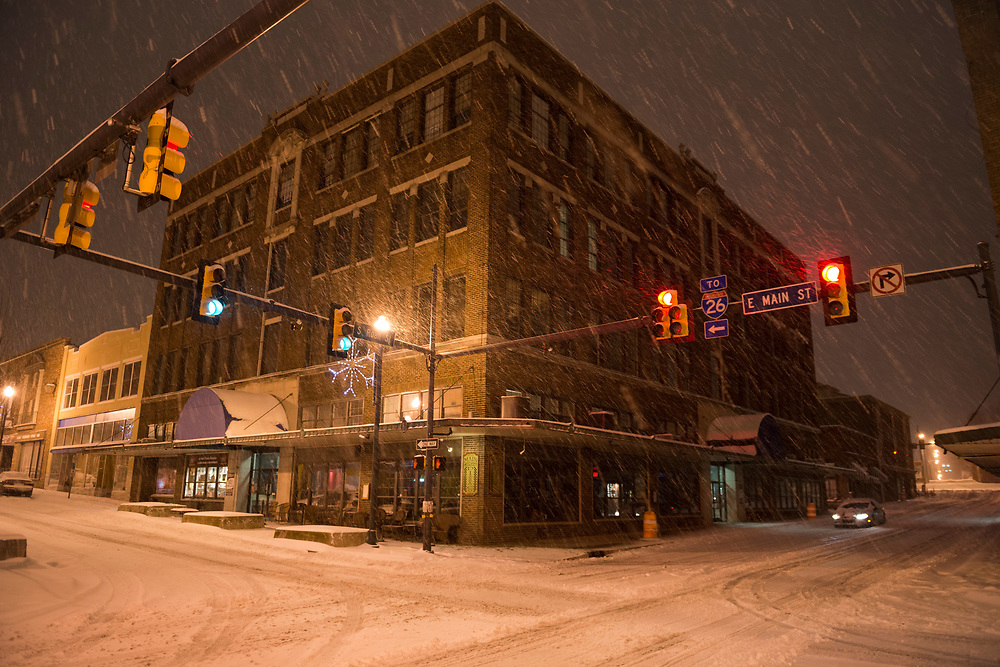 Snow falls at the intersections of Roan and E Main Streets in Johnson City, Tennessee. A lone car is driving on the street, and a pizza restaurant is on the corner. (February 12, 2014)
