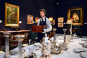 © Licensed to London News Pictures. 18/03/2013. London, UK An assistant carries a Cigar box through a room setting from the house. Press call for The Collection of Mark Birley at Sotheby's auction house today 18th March 2013. Mark Birley was the owners of members only clubs Annabel's, Mark's Club, George's Bar, Harry's Bar and The Bath and Racquets Club in London. Photo credit : Stephen Simpson/LNP