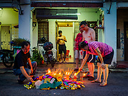 24 AUGUST 2018 - GEORGE TOWN, PENANG, MALAYSIA: A family in George Town burns ghost money in front of their home during Hungry Ghost Month. The Ghost Festival, also known as the Hungry Ghost Festival is a traditional Buddhist and Taoist festival held in Chinese communities throughout Asia. The Ghost Festival, also called Ghost Day, is on the 15th night of the seventh month (25 August in 2018). During Ghost Festival, the deceased are believed to visit the living. In many Chinese communities, there are Chinese operas and puppet shows and elaborate banquets are staged to appease the ghosts.     PHOTO BY JACK KURTZ