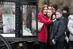 © Licensed to London News Pictures . 20/12/2017. Manchester, UK. Mourners hug and cry next to Sam's coffin in the hearse , outside the church after the service . The funeral of 14-year-old Sam Berkley at Christ Church in Denton , East Manchester . Mourners wear red and white , the colours of Hattersley FC , for whom Berkley played . Amongst their number are pupils and friends from Audenshaw School . Berkley died after being hit by a grey BMW near junction 3 of the M67 in Hyde , East Manchester , on 1st December 2017 . Photo credit: Joel Goodman/LNP