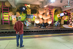 """© Licensed to London News Pictures. 07/06/2018. LONDON, UK.  A commuter views a new artwork """"my name is lettie eggyscrub"""", by British artist Heather Phillipson, unveiled at Gloucester Road Underground station filling the 80m platform.  The installation is a major commission for Art on the Underground.  Photo credit: Stephen Chung/LNP"""