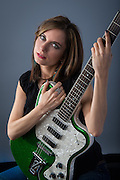 Beautiful woman with a green Fender Modena guitar