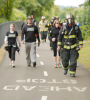 """Laconia Firefighter Chris Beaudoin donning full protective gear weighing approximately 60 lbs. participates in Saturday's WOW FEST 3 mile """"Take the Trail Fun Walk.   (Karen Bobotas/for the Laconia Daily Sun)"""