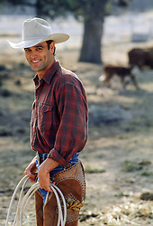 handsome cowboy smiling while standing on a ranch