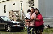 Carlos Cardona, center, stands with his partner, Karen Mayorquin, and their daughter, Kendra Mayorquin, outside their home in East Bethany, NY, Thursday, June 29, 2017. Cardona, who works at a dairy farm nearby, would like to obtain a non-citizen drivers license so that he can drive his car legally, but New York State, which has the third-largest immigrant population in the country, doesn't offer them yet. <br /> (Heather Ainsworth for The New York Times)
