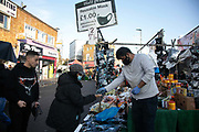 Ali selling face masks in Ridley Road Market from his stall during the second coronavirus national lockdownon on 7th November 2020, East London, United Kingdom. Only a certain number of shoppers are allowed into the market, controlled by council workers because of the corona pandemic and lockdown. The UK Government introduced a 4 week lockdown from November 5th - December 2nd to combat the coronavirus outbreak. It is the third day of the national lockdown restrictions mean that people are only allowed to meet outside, in pairs and only if keeping social distance. Only if they already live together or have formed a social bubble can they interact freely.
