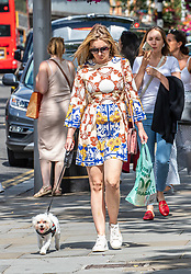 © Licensed to London News Pictures. 22/07/2020. London, UK. A dog walker enjoys the warm sunshine on the King's Road in Chelsea as weather forecasters predict 26c today as Londoners get ready for Friday when masks become compulsory in shops in England. Photo credit: Alex Lentati/LNP