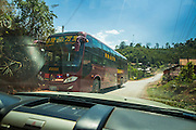 12 MARCH 2013 - ALONG HIGHWAY 13, LAOS:  A Chinese passenger bus drives south on Highway 13 in rural Laos towards Luang Prabang. The paving of Highway 13 from Vientiane to near the Chinese border has changed the way of life in rural Laos. Villagers near Luang Prabang used to have to take unreliable boats that took three hours round trip to get from the homes to the tourist center of Luang Prabang, now they take a 40 minute round trip bus ride. North of Luang Prabang, paving the highway has been an opportunity for China to use Laos as a transshipping point. Chinese merchandise now goes through Laos to Thailand where it's put on Thai trains and taken to the deep water port east of Bangkok. The Chinese have also expanded their economic empire into Laos. Chinese hotels and businesses are common in northern Laos and in some cities, like Oudomxay, are now up to 40% percent. As the roads are paved, more people move away from their traditional homes in the mountains of Laos and crowd the side of the road living off tourists' and truck drivers.    PHOTO BY JACK KURTZ