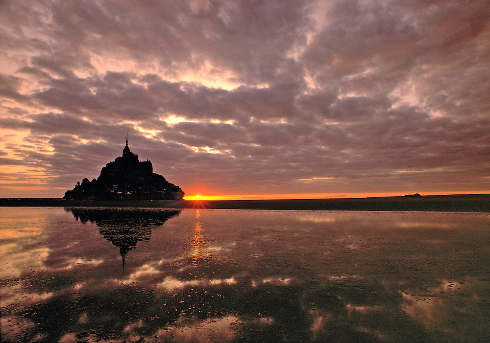 The setting sun silhouettes Mont St. Michel in Normandy, France.