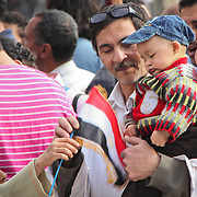 A young boy hands a small child an Egyptian flag to wave during the Day of Justice and Cleansing in Cairo's Tahrir Square.