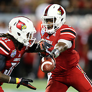 Louisville Cardinals quarterback Teddy Bridgewater (5) hands off the football to Louisville Cardinals running back Senorise Perry (32)is seen during the NCAA Football Russell Athletic Bowl football game between the Louisville Cardinals and the Miami Hurricanes, at the Florida Citrus Bowl on Saturday, December 28, 2013 in Orlando, Florida. (AP Photo/Alex Menendez)