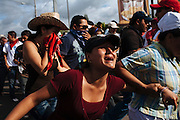 A woman cries and walks away while others cover their mouths to protect themselves from tear gas during a clash against the military coup near Toncontin international airport in Tegucigalpa on July 5, 2009.