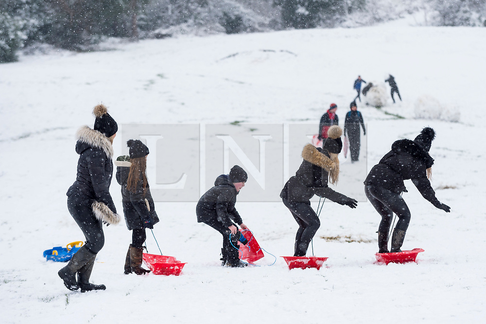 © Licensed to London News Pictures. 24/01/2021. LONDON, UK.  People having fun sledding on a covered golf course as the first snow fall of the year arrives in Northwood, north west London.  Photo credit: Stephen Chung/LNP