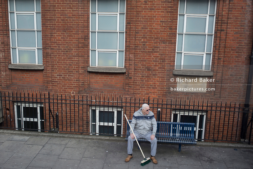 A man sits on a public bench with a new long-handled brush on the Walworth Road, on 5th March 2019, in London, England.