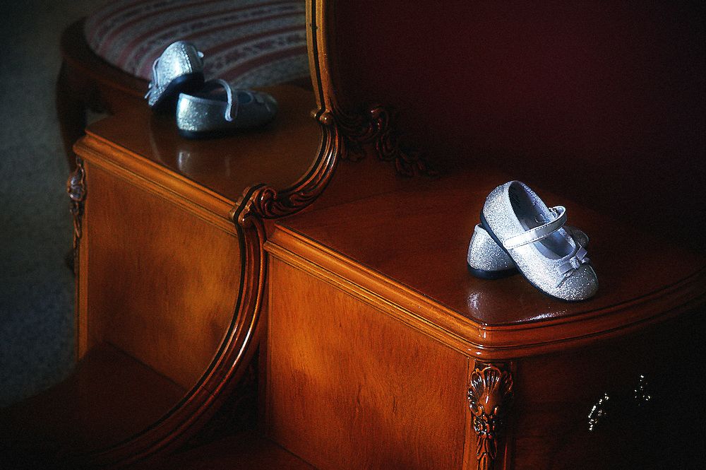 Girl's dress shoes reflected in mirror.