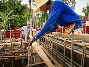 06 SEPTEMBER 2013 - BANGKOK, THAILAND: Workers install forms for walls at a construction site in the Bang Na section of Bangkok near Suvarnabhumi International Airport. The workers are building a four storey apartment building. They will live on the site for approximately one year, until the building is close to opening. They are paid the Thai minimum wage of 300 Baht per day, approximately $10 US. They live on the site rent free and don't pay to use electricity, both are provided by the project owner.               PHOTO BY JACK KURTZ