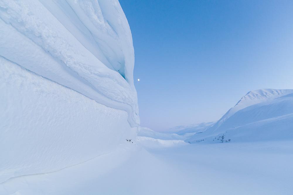 View up windswept snow banks in Foxdalen, Svalbard.
