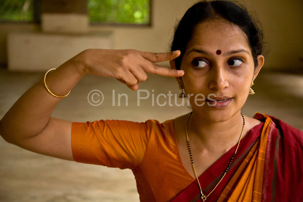 """Ganga Thampi, teaches young  trainee dancers  movement, rhythm and expression, known as """"nritya"""" and seen here a lesson in """"abhinaya"""", or stylized expressions at the traditional and highly prestigious Kalakshetra school for the arts, Chennai. The school was founded in 1936 and due to its exacting and demanding schedule is considered India's formost classical dance academy of this ancient cultural art heritage that is informally known as """"temple dancing"""" and that dates back to the Natya Shastra, the 2000 year old text that lays down the principles of Indian dramatic theory and performance. Tamil Nadu, India."""