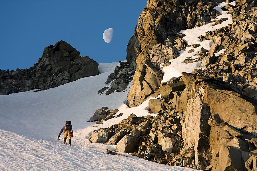 Climber Jim Prager ascends towards the moon and the NE Arete of Wedge Mountain in Garibaldi Provincial Park, British Columbia, Canada on June 14, 2009.