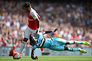 Alex Oxlade-Chamberlain of Arsenal runs past Cheikhou Kouyate of West Ham United as he falls to the ground. Barclays Premier League, Arsenal v West Ham Utd at the Emirates Stadium in London on Sunday 9th August 2015.<br /> pic by John Patrick Fletcher, Andrew Orchard sports photography.