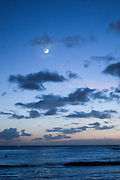 The moon over the ocean at dusk in Hawaii.